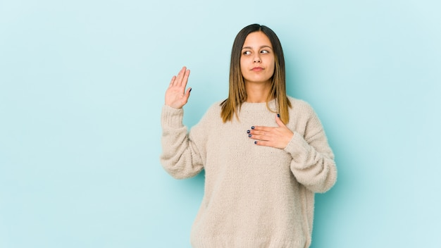 Молодая женщина на синей стене принимая присягу, положив руку на грудь.