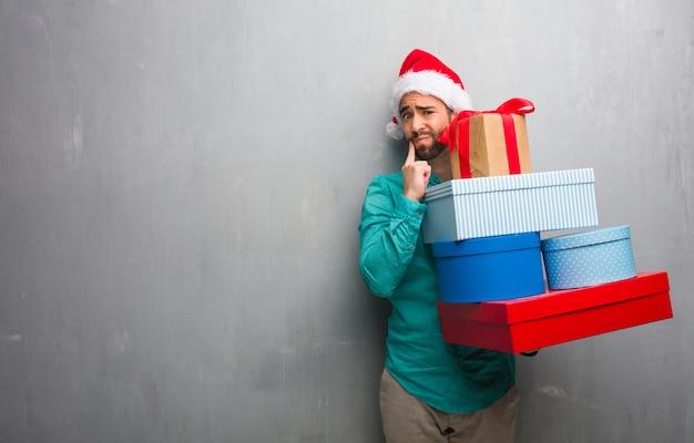 疑惑と混乱の贈り物をしているサンタの帽子を身に着けている若い男