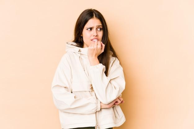 爪をかむベージュの壁に若い白人女性、神経質で非常に不安。