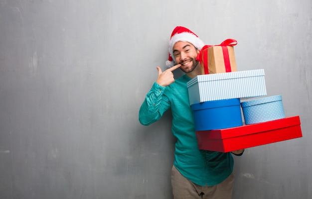 Молодой человек в шляпе санта, проведение подарки улыбки, указывая рот