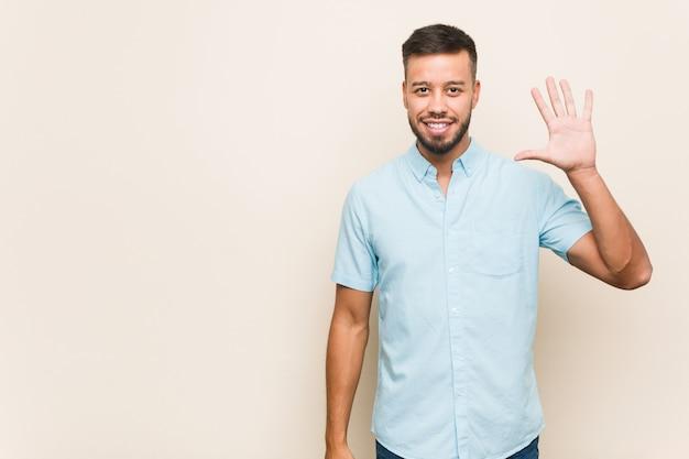 Молодой человек южной азии, улыбаясь веселый показ номер пять с пальцами.