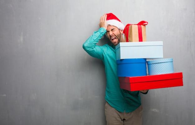 Молодой человек в шляпе санта держит подарки забывчивый, реализовать что-то
