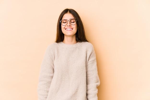 Молодая кавказская женщина на бежевой стене смеется и закрывает глаза, чувствует себя расслабленной и счастливой.