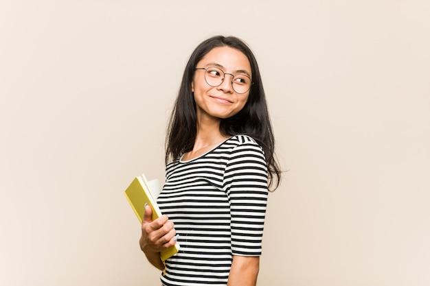 Молодой азиатский студент женщины держа книгу смотрит в сторону усмехаясь, жизнерадостный и приятный.