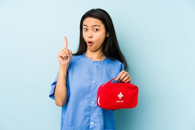 Молодая китайская женщина медсестры на синей стене громко смеется, держа руку на груди.