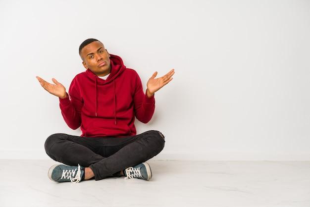 疑い、ジェスチャーを質問で肩をすくめて床に座っている若いラテン男。
