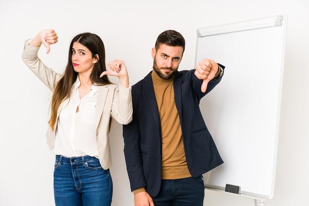 親指ダウンを示すと嫌悪感を表現する若い白人ビジネスカップル。