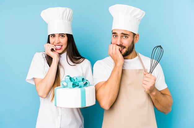 Молодая пара готовит торт вместе человек, указывая рукой на пустое пространство рубашки, гордый и уверенный
