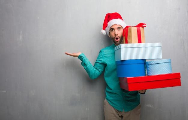 Молодой человек, носить шляпу санта, проведение подарки, что-то на ладони