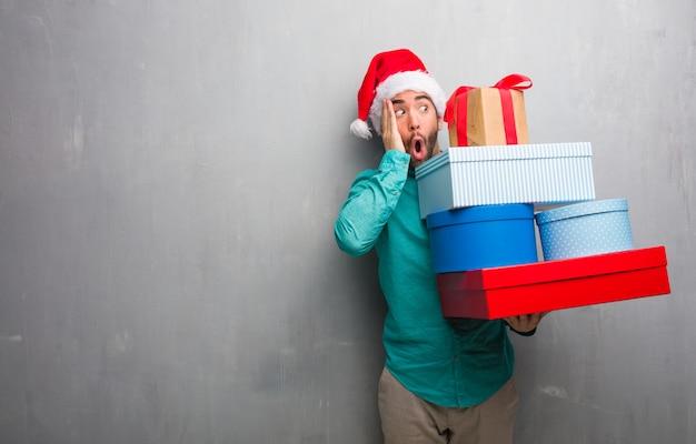 Молодой человек в шляпе санта с подарками удивлен и потрясен