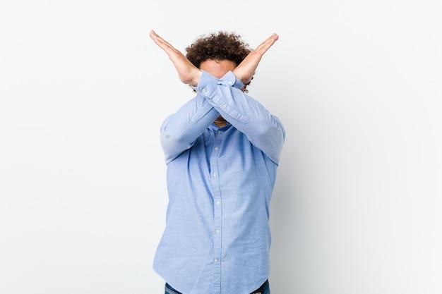 Молодой кудрявый зрелый человек в элегантной рубашке, скрестив руки