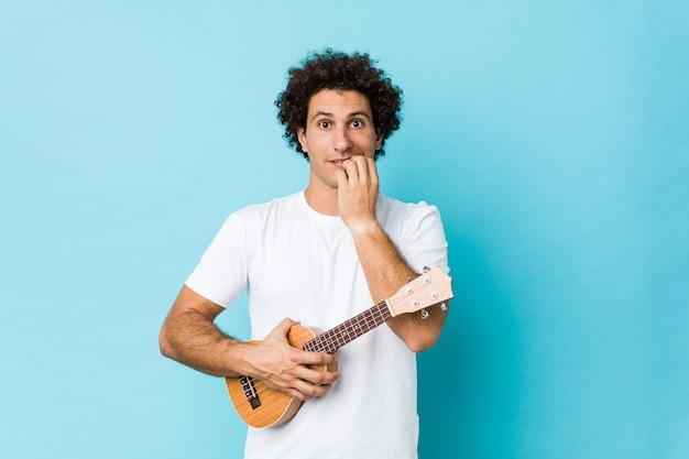 爪をかむウクレレを演奏する若い白人の巻き毛の男、神経質で非常に心配しています。