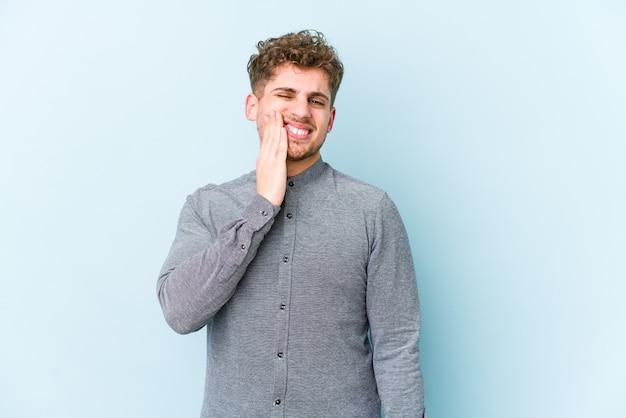 強い歯の痛み、臼歯の痛みを持つ若い金髪巻き毛の白人男性。