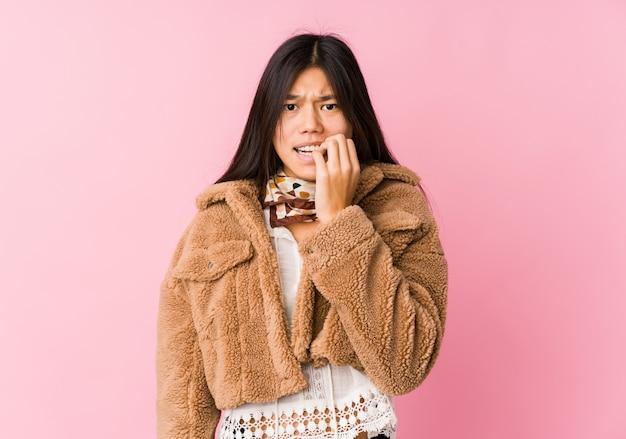 爪をかむ若いアジア女性、神経質で非常に不安。
