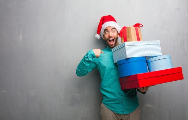 Молодой человек в шляпе санта с подарками удивлен, чувствует себя успешным и процветающим