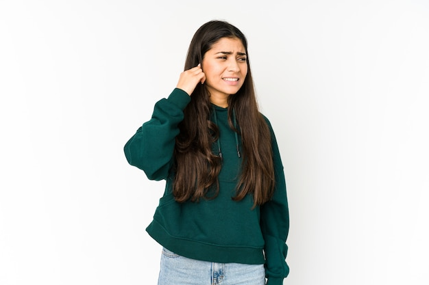 手で耳を覆う紫の壁に若いインド人女性。