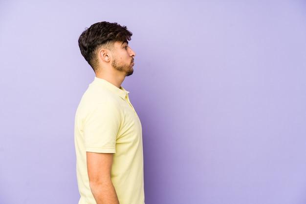 Молодой аравийский человек на фиолетовую стену, глядя влево, сбоку позе.