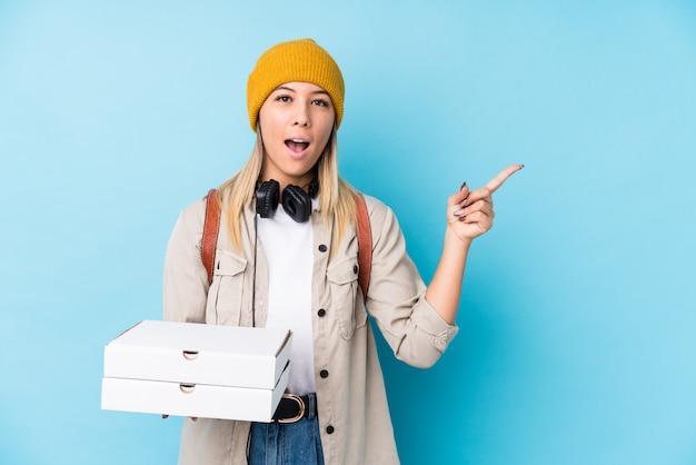 側を指しているピザを保持している若い白人女性
