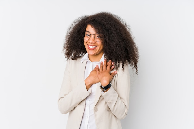 Молодая афро-американская бизнес-леди имеет дружелюбное выражение, отжимая ладонь к груди.