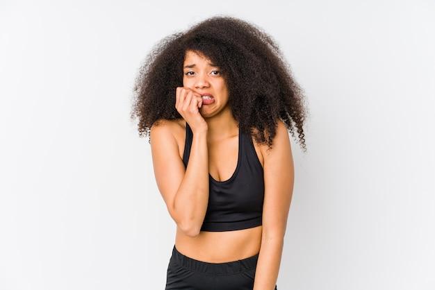 爪をかむ若いアフリカ系アメリカ人のスポーティな女性、神経質で非常に心配しています。