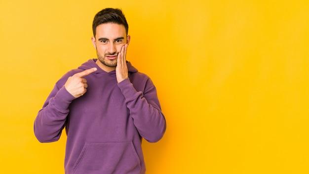 強い歯の痛み、臼歯の痛みを持つ黄色の壁に若い白人男。