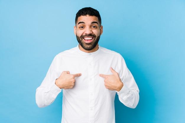 Молодой человек латинской против голубой стены удивлен, указывая пальцем на себя
