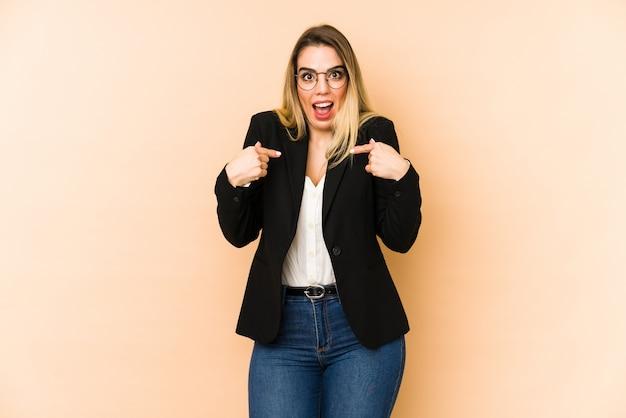 ベージュの壁に中年ビジネス女性が自分で指で指しているを驚かせた