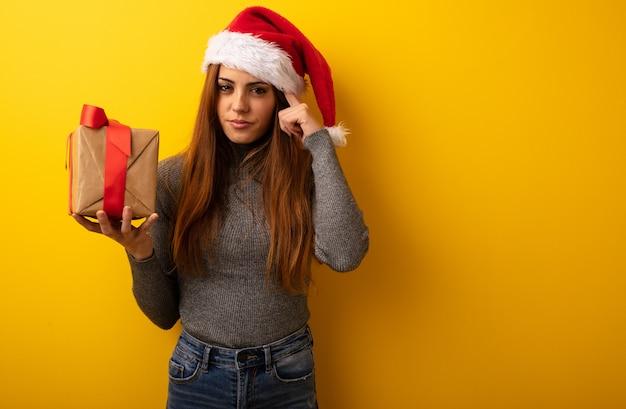Молодая красивая женщина с подарком делает жест концентрации