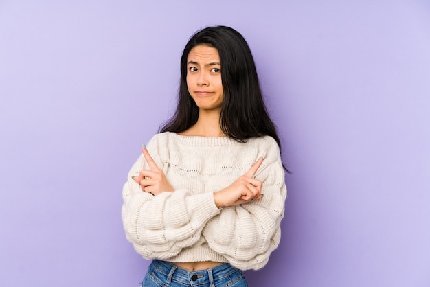 Молодая китаянка на фиолетовой стене указывает в сторону