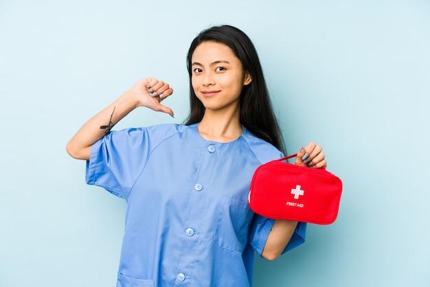 救急箱を押しながら自分自身を指している青い壁に若い中国の看護師