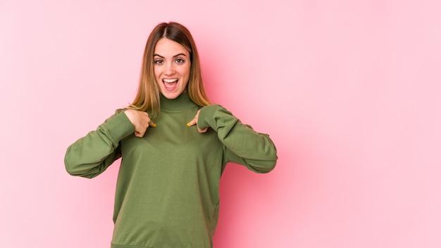 Кавказская девушка на розовой стене удивлен, указывая пальцем, широко улыбаясь.