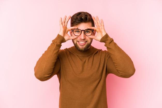 Молодой кавказский человек на розовой стене держа глаза открытыми