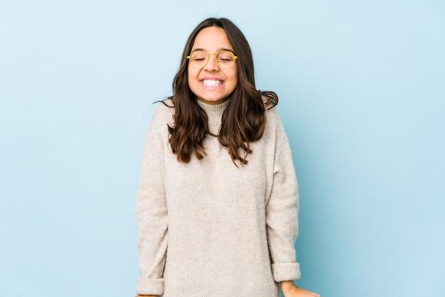 Молодая испанская женщина смеется и закрывает глаза, чувствует себя расслабленной и счастливой.