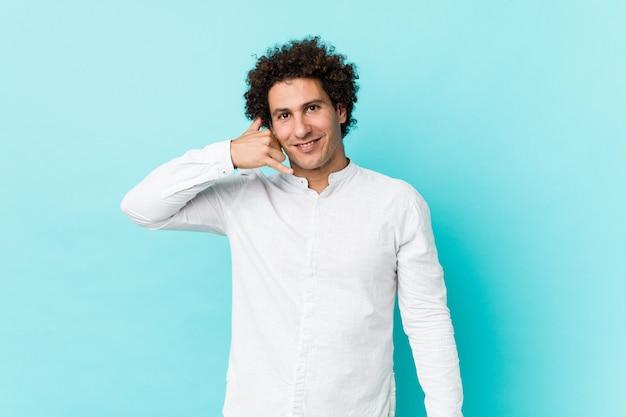 Молодой курчавый зрелый человек нося элегантную рубашку показывая жест звонка мобильного телефона с пальцами.