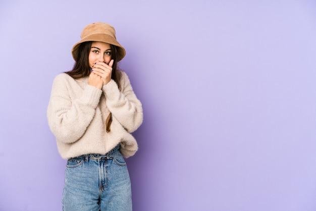 Молодая кавказская женщина изолированная на фиолетовом рте заволакивания при руки смотря потревоженный.