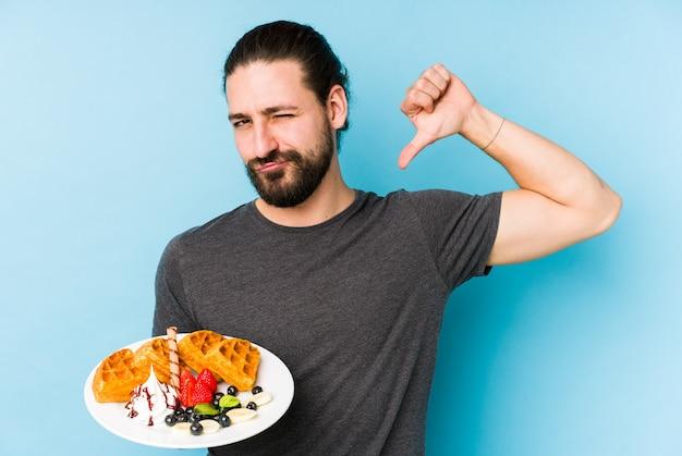 孤立したワッフルデザートを食べる若い白人男性は、次の例のように誇りと自信を感じています。