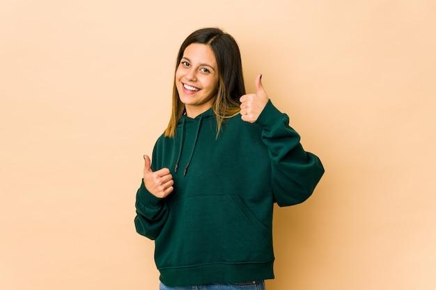 Молодая женщина, изолированных на бежевом, поднимая оба больших пальца вверх, улыбаясь и уверенно.