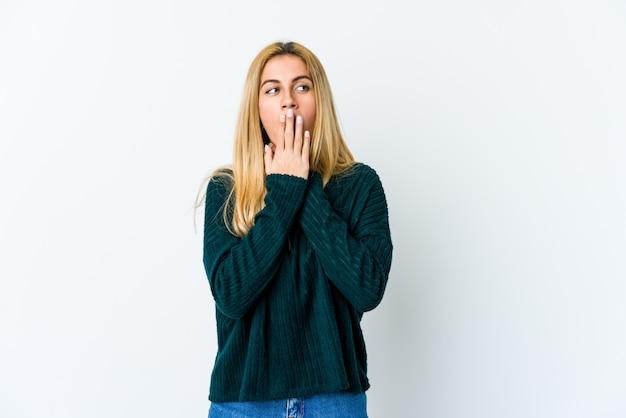 白で隔離される若いブロンドの女性は、ウイルスや感染症のため喉の痛みに苦しんでいます。