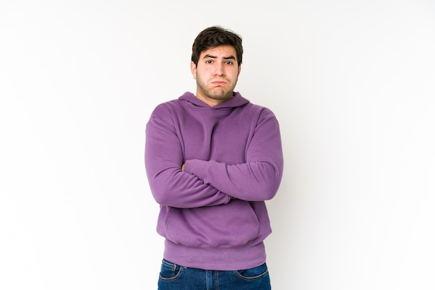 白で隔離される若い男は頬を吹く、疲れた表情をしています。表情のコンセプト。