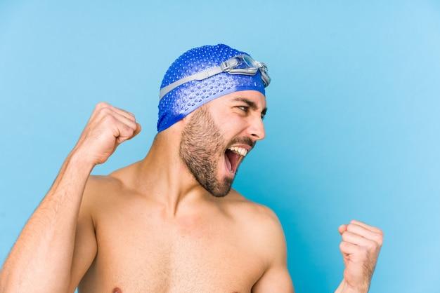 Молодой красивый человек пловца изолировал поднимать кулак после победы, концепцию победителя.