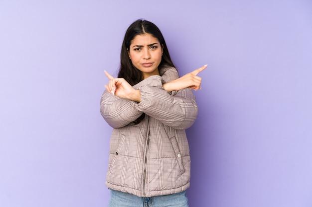 Молодая индийская женщина, изолированных на фиолетовые точки боком, пытается выбрать между двумя вариантами.
