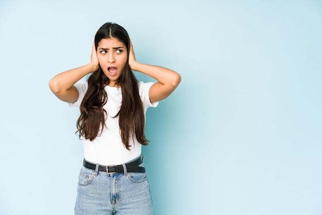 あまりにも大きな音を聞かないようにしようと手で耳を覆う青の若いインド人女性。