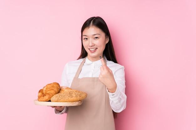 Молодая китайская женщина пекаря изолировала указывать пальцем на вас как будто приглашая приблизиться.