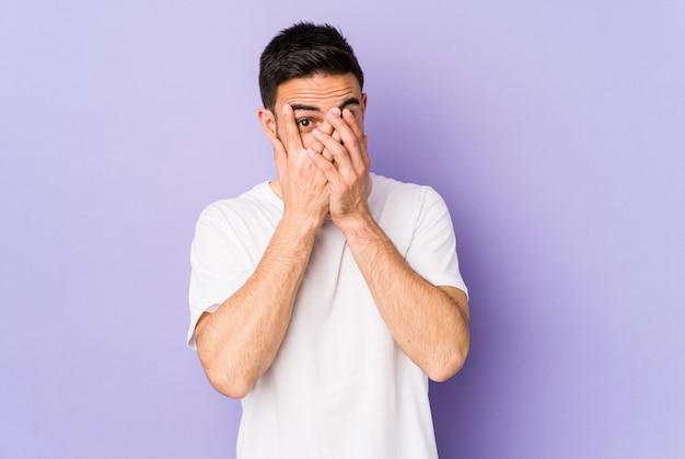 恐怖と緊張の指の間で紫色の点滅に分離された若い白人男。