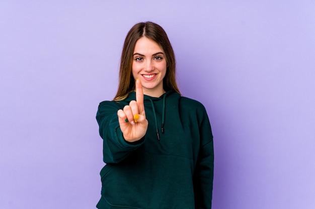 指でナンバーワンを示す紫色に分離された若い白人女性。
