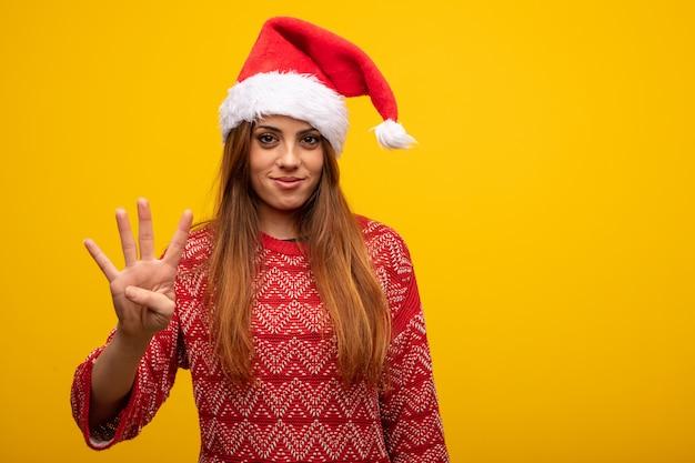 Молодая женщина в шляпе санта показывает номер четыре