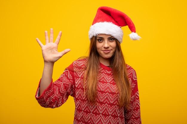 Молодая женщина в шляпе санта показывает номер пять