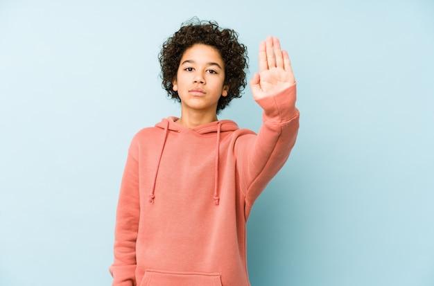 アフリカ系アメリカ人の少年は、一時停止の標識を示す伸ばした手で立って、あなたを誇示します。