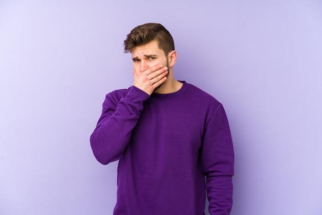 Молодой кавказский человек изолированный на фиолетовом рте заволакивания при руки смотря потревоженный.