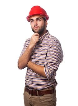 赤いヘルメットと物思いにふける男